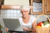 Elderly woman in kitchen with laptop computer — Stock Photo