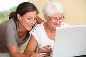 Elderly woman and young woman shopping on internet — Stock Photo