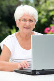 Elderly woman with laptop computer — Stock Photo