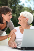 Elderly woman and young woman surfing on internet — Stock Photo