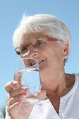 Elderly woman drinking wate — Stock Photo