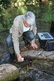 Biologist testing quality of stream water — Stock Photo
