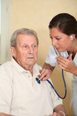 Elderly person with nurse — Stock Photo