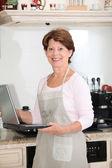 äldre kvinna i köket med bärbar dator — Stockfoto