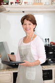 Senior woman in kitchen with laptop computer — Stock Photo