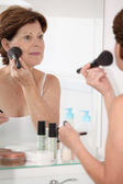 Senior woman putting makeup — Stockfoto