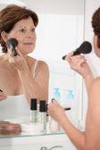 Starszy kobieta wprowadzenie makijaż — Zdjęcie stockowe