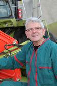 Farmer standing by harvester — Stock Photo