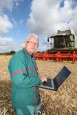 Granjero de pie en el campo de trigo con computadora — Foto de Stock