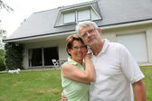 Senior couple standing in front of a house — Stock Photo