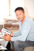 Man sitting in couch with book — Stock Photo