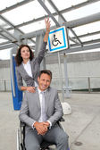 Businesswoman with man in wheelchair — Stock Photo