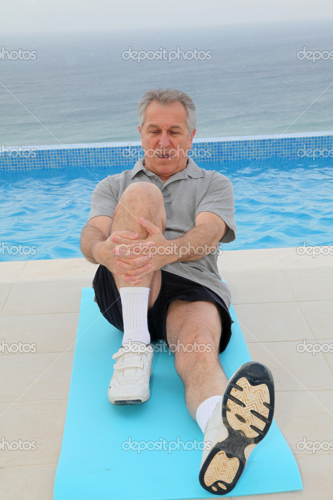 Senior man doing exercises by a swimming-pool — Stock Photo #6700159