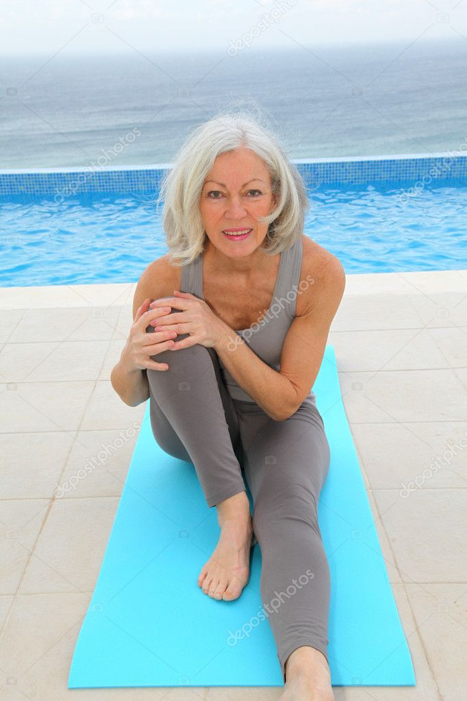 Senior woman doing exercises by a swimming-pool  Stock Photo #6700166