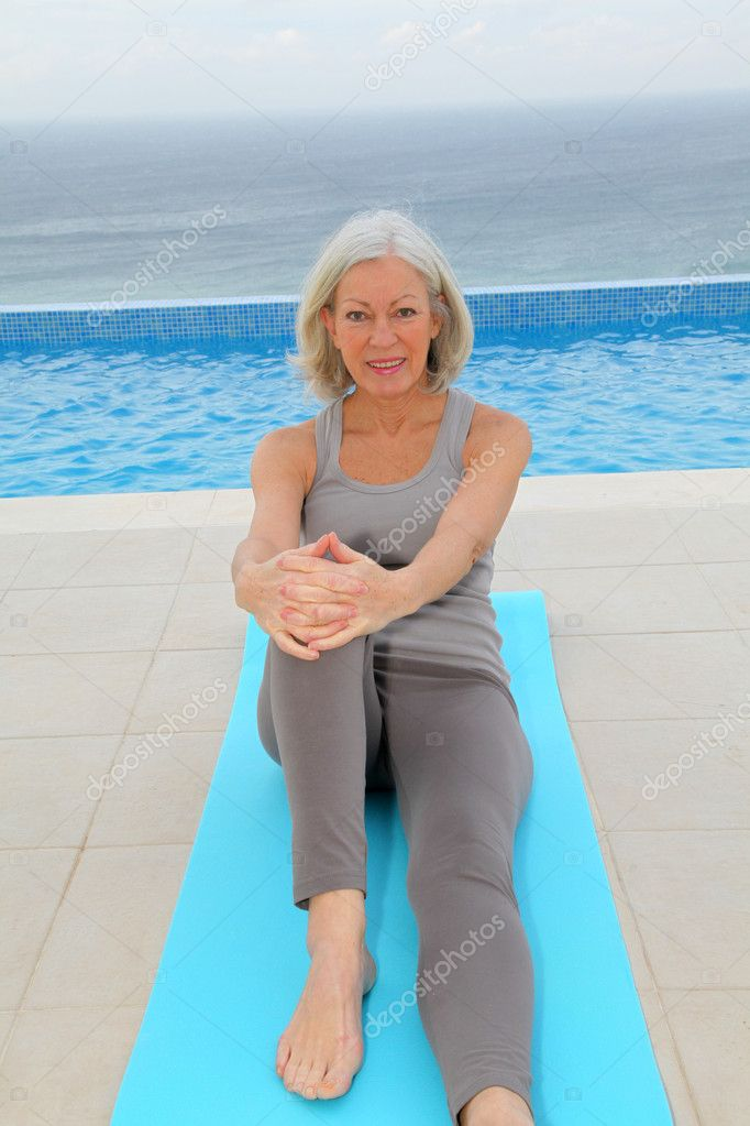 Senior woman doing exercises by a swimming-pool — Stock Photo #6700167