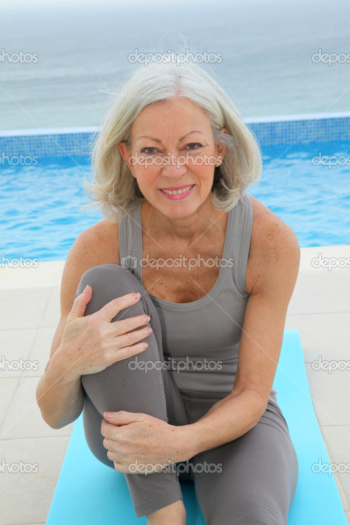 Senior woman doing exercises by a swimming-pool — Stock Photo #6700171
