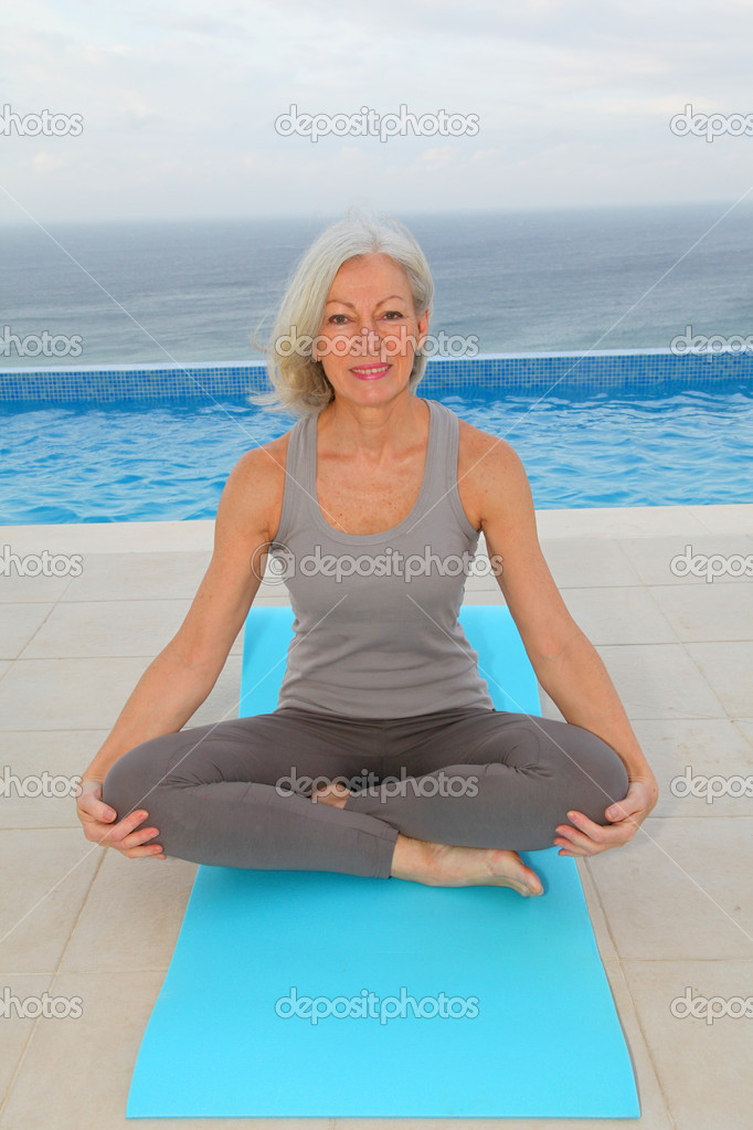 Senior woman doing exercises by a swimming-pool — Stock Photo #6700175