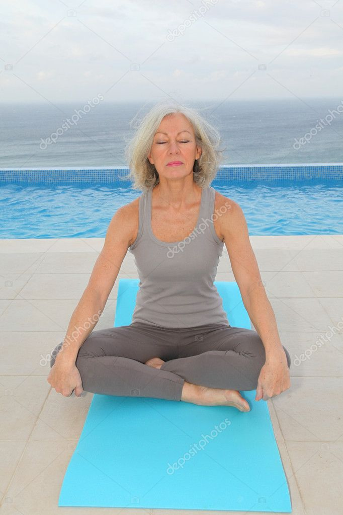 Senior woman doing exercises by a swimming-pool — Stock Photo #6700177