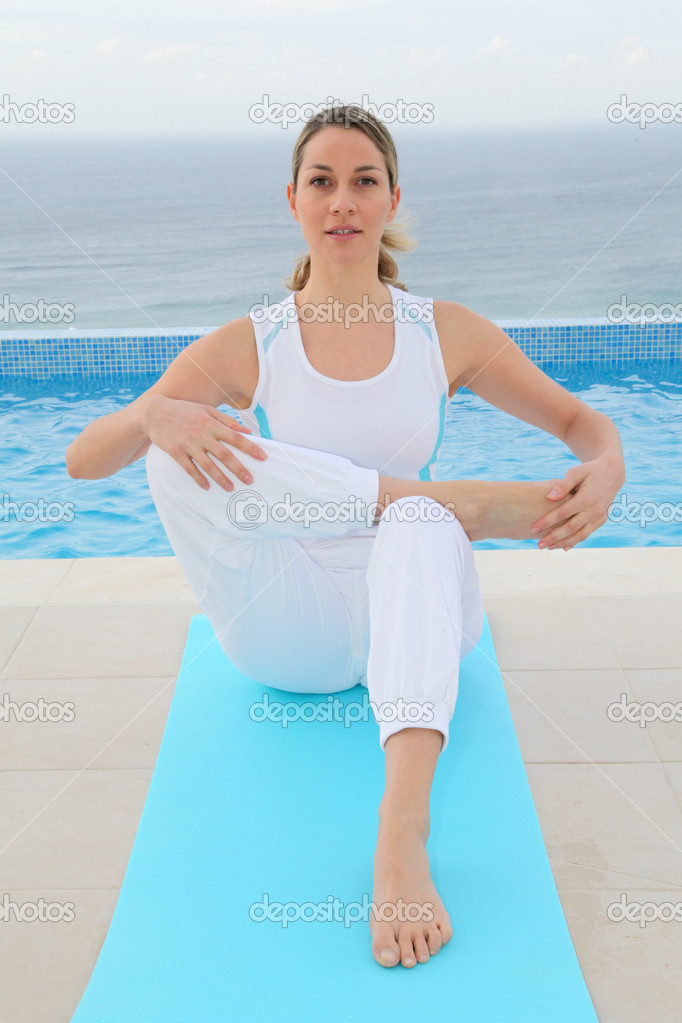 Woman doing exercises by a swimming-pool — Stock Photo #6700193
