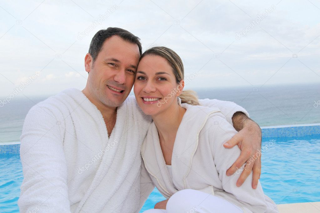 Couple in bathrobe sitting by swimming-pool — Stock Photo #6700204