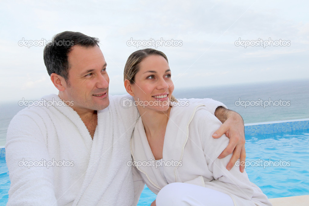 Couple in bathrobe sitting by swimming-pool — Stock Photo #6700208