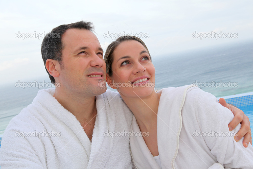 Couple in bathrobe sitting by swimming-pool — Stock Photo #6700209