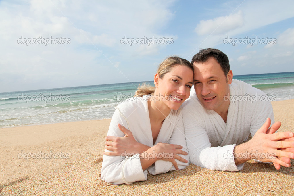 Couple relaxing in bathrobe at the beach — Stock Photo #6700473