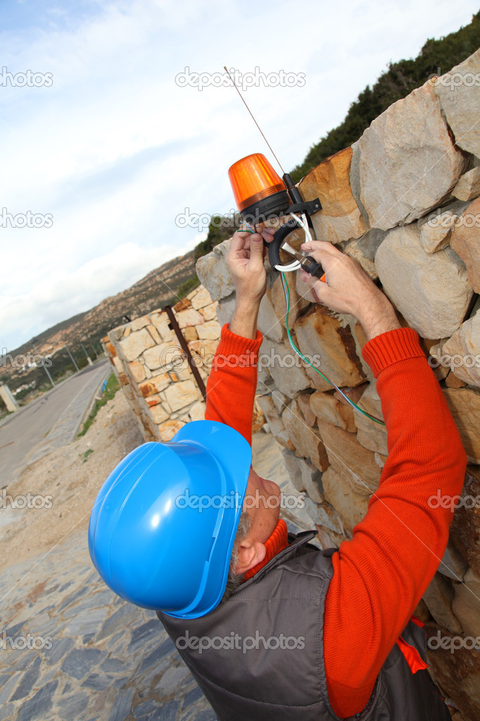 Worker with security helmet installing gate system  Stock Photo #6700663