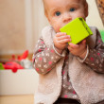 Baby holding a green block facing camera — Stock Photo