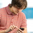 Portrait of a trendy young guy typing a message on mobile phone — 图库照片