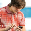 Foto de Stock  : Portrait of a trendy young guy typing a message on mobile phone
