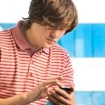 一个时髦的年轻小伙子,在移动电话上键入一条消息的肖像 — 图库照片