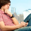Portrait of a trendy young guy typing a message on mobile phone — Stock Photo #5740793