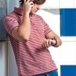Foto Stock: Portrait of young mchecking time while talking on cellphone