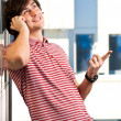 Smiling young man speaking on cellphone — Stock Photo