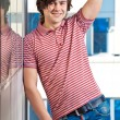 Happy young man raising hand against the window — Stockfoto