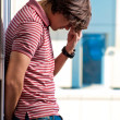 Depressed young man standing against window in the background — Stok fotoğraf