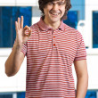Happy young mindicating OK sign against window — Stockfoto #5740811
