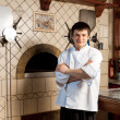 A young chef standing next to oven — Stockfoto