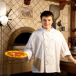 A young chef standing next to oven — Stok fotoğraf