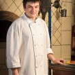 A young chef standing next to oven — Foto de stock #5740944