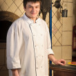 A young chef standing next to oven — Stock Photo #5740944