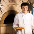 A young chef standing next to oven — Stock Photo #5740947