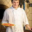 Photo: A young chef standing next to oven