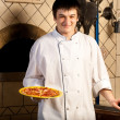 A young chef standing next to oven — ストック写真