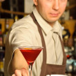 Stock Photo: A barman holding the glass with cocktail