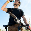 Closeup of a young biker drinking water — Foto de Stock