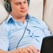 Casual man listening music with headphones at home — Stock Photo #5741653
