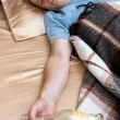 A young man sleeping on the couch with a bottle of wiskey — Stockfoto