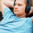 Laying young man listening music — Stock Photo